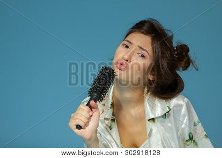 Cheerful attractive teen girl sing song holding comb like a microphone in the morning, over blue background.