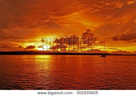 A Bright Inspirational Panoramic Orange Coloured Cumulus Cloudy Sunrise Seascape Over Sea Water With