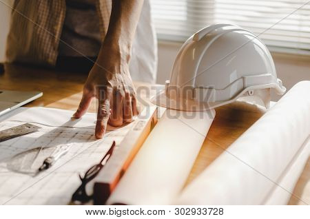 Professional Architect, Engineer Or Interior Planning Construction With Blueprint On Workplace Desk