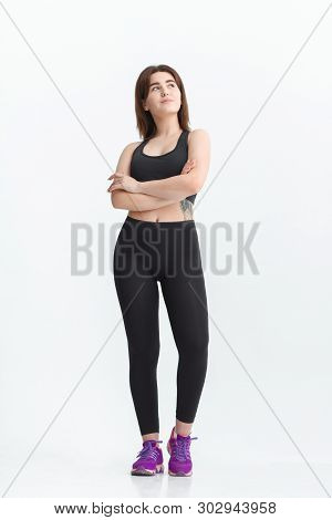 Woman With Dark Hair In A Sportswear Stretching In A Gym. Exercising For Weight Loss