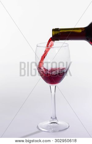 Pouring Red Wine Into The Glass On White Background