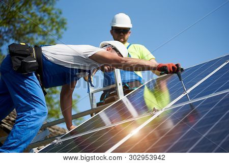 Two Professional Technicians Installing Solar Photo Voltaic Panel To Metal Platform On Blue Sky Back