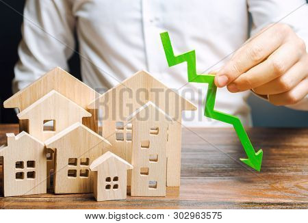 Analyst Holds Down Arrow Near The Wooden Houses. Concept Of Falling Real Estate Market. Low Prices A
