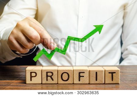 Wooden Blocks With The Word Profit And An Up Arrow. Concept Of Business Success, Financial Growth An