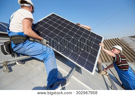 Male Workers Installing Stand-alone Solar Photovoltaic Panel System. Electricians Lifting Blue Solar