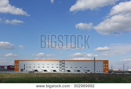 Industrial Building, Warehouse. Blue Sky With Clouds.