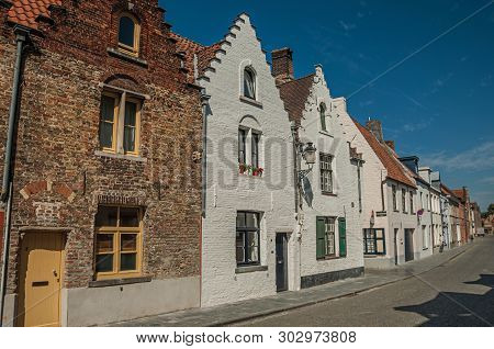 Bruges, Belgium - July 05, 2017. Brick Facade Of Old Houses With A Blue Sky In An Empty Street Of Br