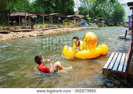 Boys Enjoy And Has Fun Rowing Downstream On Canal