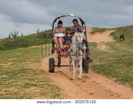 Tourists Traveling In A Horse-drawn Carriage Near Jericoacoara On Brazil