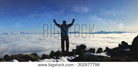 Back View Of Tourist Hiker With Raised Arms Standing On Rocky Hill On Copy Space Background Of Beaut