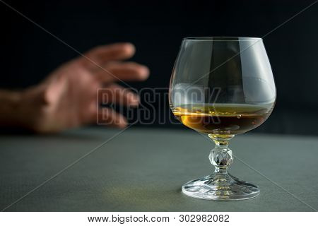 Hand Reaches For A Glass Of Whiskey Or Cognac Or Alcohol Drink, Alcoholism And Alcohol Abuse Concept