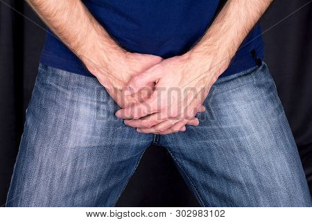 Sexual Disorders Erectile Dysfunction Concept. Close Up Of A Man With Hands Holding His Crotch Dark