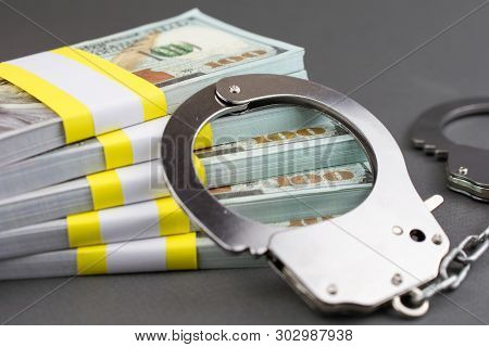 Money And Handcuffs. Financial Crime, Advance Fee Scams, Card Fraud, Counterfeit Cards, Fake Check S