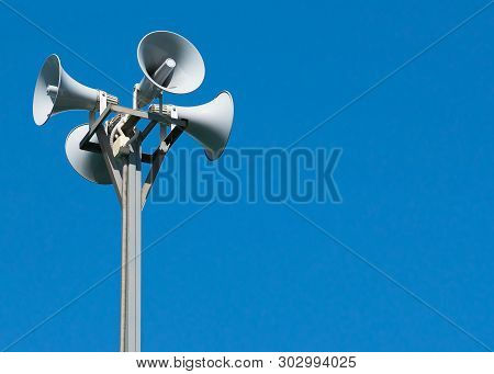 A Tall Column With Four Gray Loudspeakers In A Circle Against A Clean Blue Sky. Hazard Warning Syste