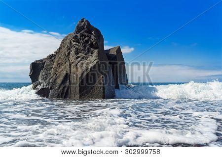 Sea Waves Splashing On The Rock Formation On Sunny Day. Praia Formosa Beach, Funchal, Portuguese Isl