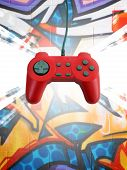 A red game controller over a graffiti background. This file includes the clipping path for the controller. poster