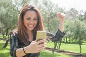 Excited euphoric lady with smartphone celebrating great news Happy woman staring at phone screen in surprise, smiling and raising fist in win gesture. Surprising good news or concept poster
