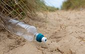 A carelessly discarded plastic drinks bottle lies amongst sand and sedge grass in fragile dunes at a beach causing pollution poster
