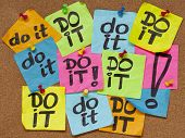 fighting procrastination concept - do it phrase on color sticky notes posted on a cork bulletin board poster