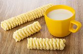 Pieces of cornflake pigtails, yellow cup with milk on wooden table poster