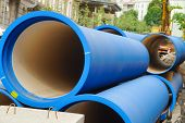 Corrugated water pipes of blue color, large diameter, prepared for laying. Lying on the street poster