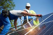 Two professional technicians installing solar photo voltaic panel to metal platform on blue sky background. Stand-alone solar system installation, efficiency and professionalism concept. poster