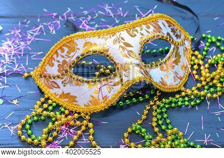 Mardi Gras Mask And Beads On A Wooden Background. Madi Gras Carnival Accessories, Confetti, Festive,