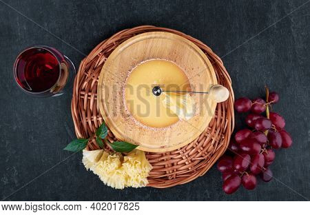 Gourmet Tasty Cheese Tete De Moine, A Glass Of Red Wine And A Bunch Of Grapes, Top View, Shallow Dep