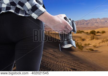 Professional Photographer Or Hobbyist Traveling Through A Desert Landscape And Holding A Camera.  Th