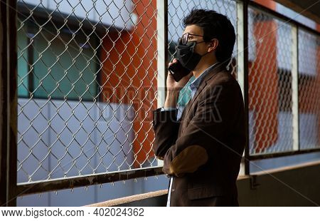 Young Men With Mask, He Is Sitting On Meal Stairs, He Has His Hands In The Mask And He Is Worried.