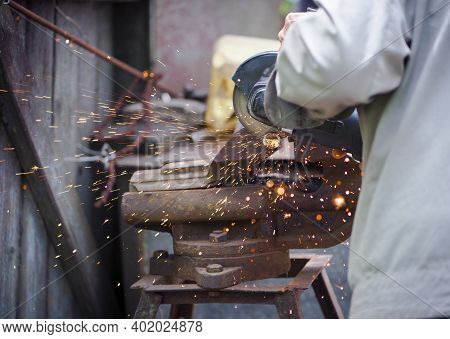 Cutting A Metal Pipe With A Splash Of Spark. The Pipe Is Clamped In A Vice. Man's Hands Hold A Grind