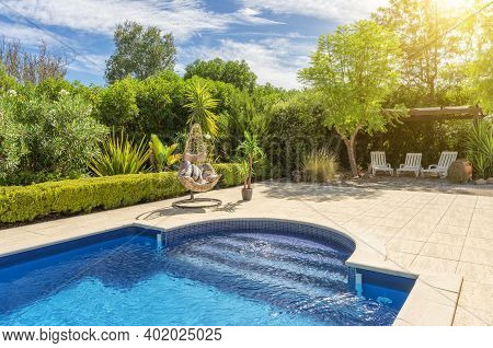 Luxurious Pool In The Garden Of A Private Villa, Hanging Chair With Pillows For Leisure Tourists, In