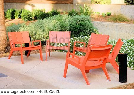 Outdoor Chairs Surrounded By Manicured Plants Taken On A Patio At A Garden In A Residential Yard