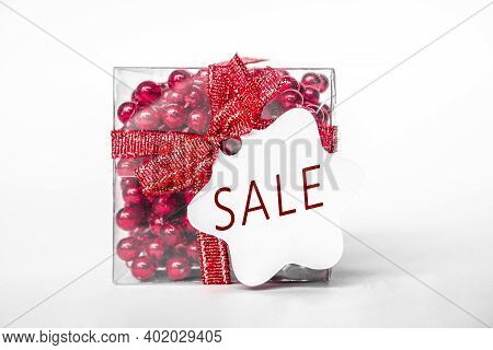 Red Gift Box With Red Ribbon, Red Beads, Bow. White Paper Tag With Text Sale, Isolated On White Back