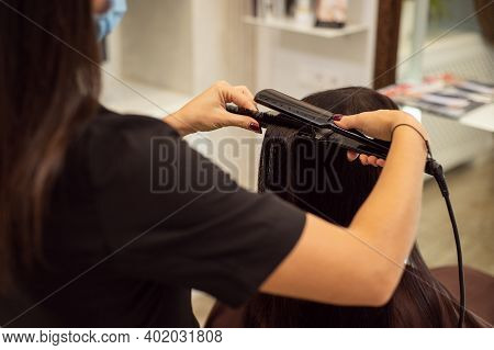 A Hairdresser In Black Uniform Makes A Hairstyle Using A Hair Straightener