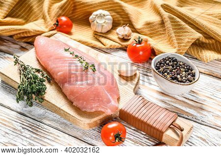 Raw Turkey Breasts On A Cutting Board. Fillet Steak. White Wooden Background. Top View
