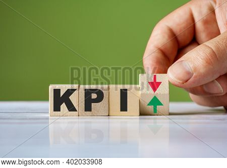 The Hand Turn Wooden Block With Red And Turn;green Arrow As Change Concept Of Kpi. Word Kpi Conceptu