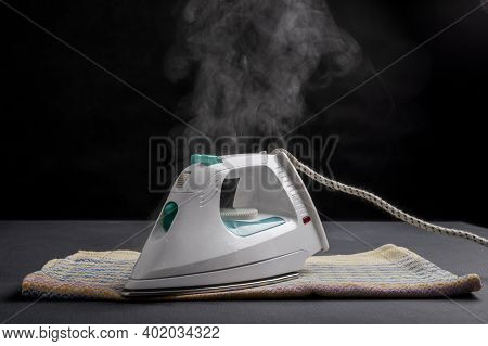 White Iron On A Towel. Steam Escaping From The Ironing Machine.