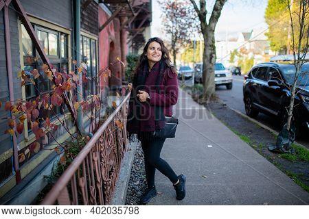 Beautiful Woman Walking On The Sidewalk Next To A Pink Handrail