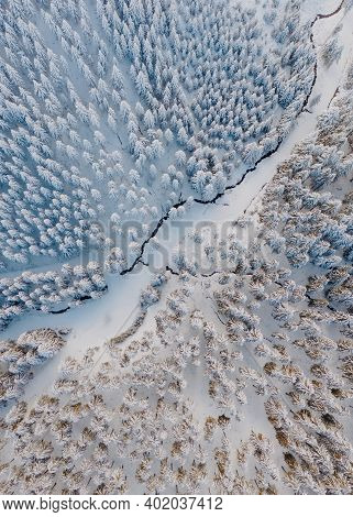 Aerial View Of The Forest And River At Winter. Snow Covered Trees In The Freezing Cold.