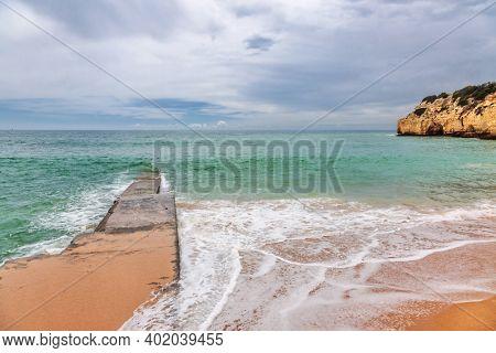 Sandy beach with stony ridges overcast weather view on Atlantic rocky coast, Algarve, Portugal.