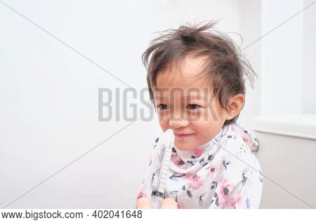 Asian Parent Flushing Her Sick Happy Little Toddler Baby Girl Child Nose With Syringe For Nasal Irri