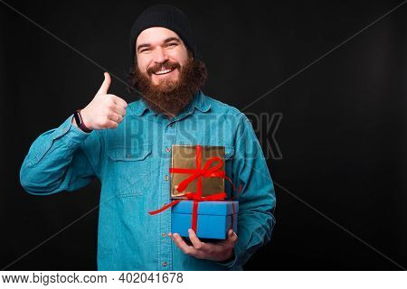 A Happy Bearded Man Is Smilng At The Camera And Holding A Thumb Up And Some Gifts Is Showing That He