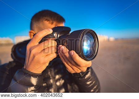 Close Up Of Professional Photographer Taking Picture With His Camera