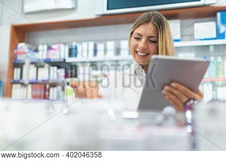 Young female pharmacist checking the inventory in a pharmacy