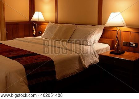 Pillows And Blanket In Bed With Light From Lamps In Vintage Bedroom At Night