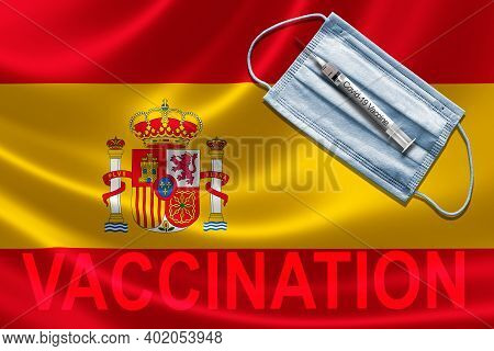 Covid-19 Vaccination In Spain Concept With Face Mask And Syringe Needle Vaccine On Spanish Flag.