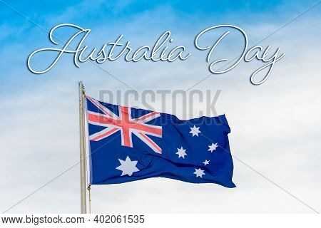 Australian Flag Australian Flag Blowing In The Wind With Australia Day Written On The Sky.