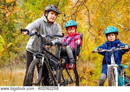 Family Cycling In Golden Autumn Park, Active Father And Kids Ride Bikes, Family Sport And Fitness Ou