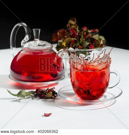 Autumn Evening Teatime With Splash In Red Herbal Tea Cup, Transparent Tea Pot With Hawthorn Berries,